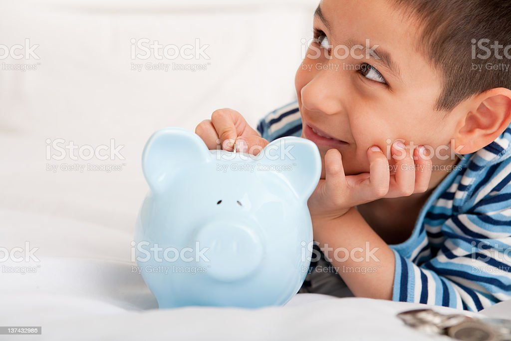 Smiling boy putting money in piggy bank stock photo