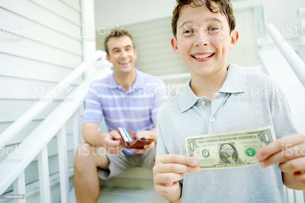 Smiling boy receives pocket money from his dad stock photo