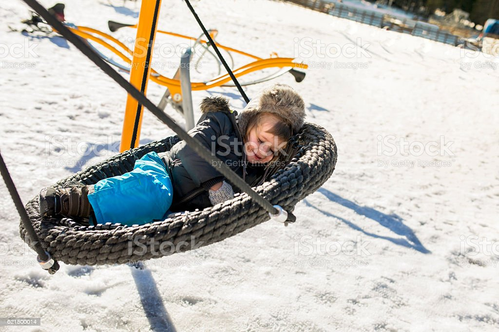 Smiling boy relaxing in knitted swing on a winter day. foto stock royalty-free