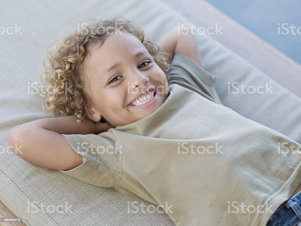 Smiling boy relaxing on patio bench royalty-free stock photo