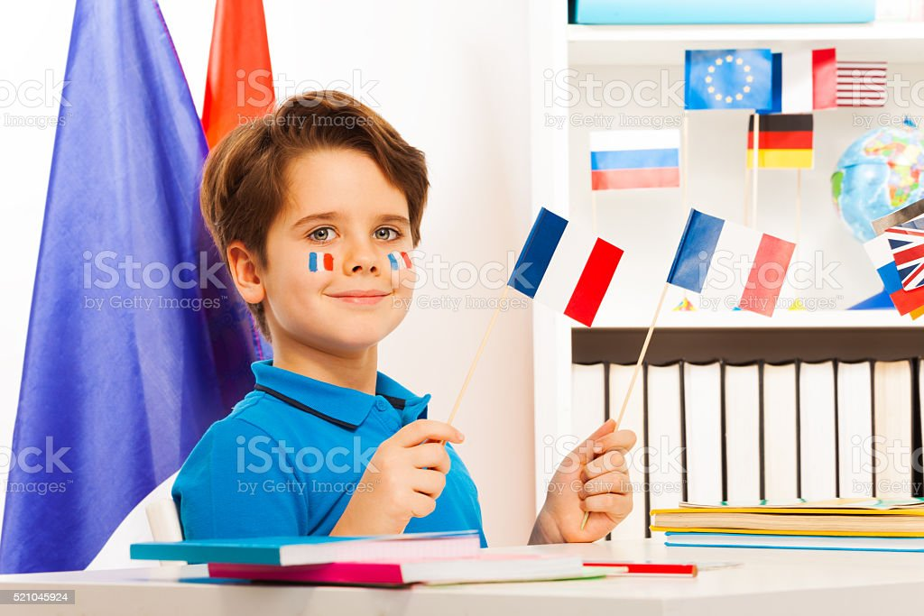 Smiling boy sitting at desk holding French flags stock photo
