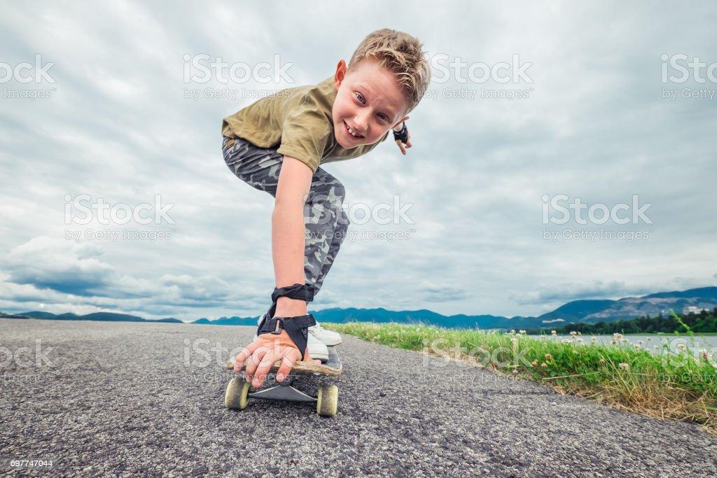 Smiling boy skates on skateboard stock photo