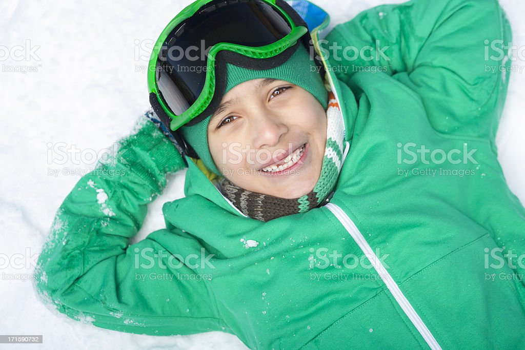 Smiling boy snowboarder laying on snow royalty-free stock photo