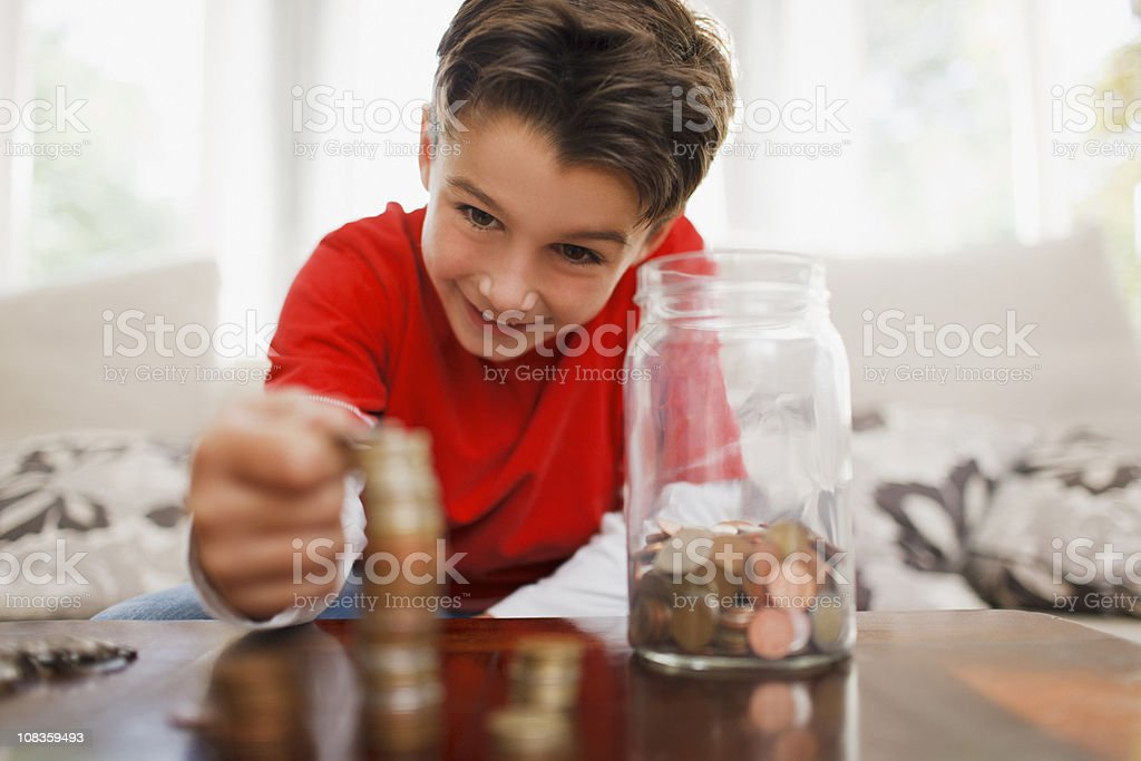 Smiling boy stacking coins royalty-free stock photo
