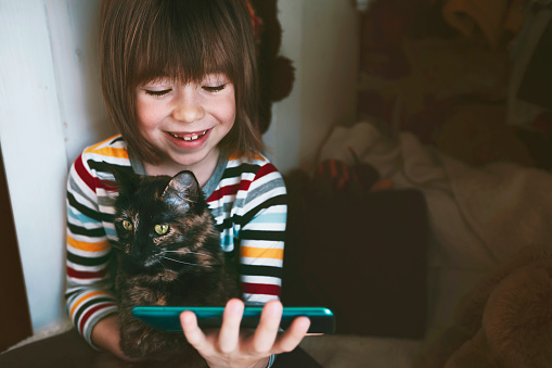 Cute smiling boy taking selfie with cat