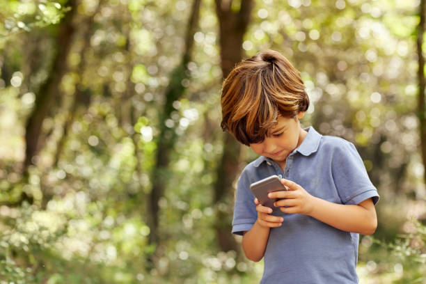 smiling boy using mobile phone in forest - kids phones stock photos and pictures