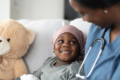 Smiling boy with cancer comforted by female doctor of African descent