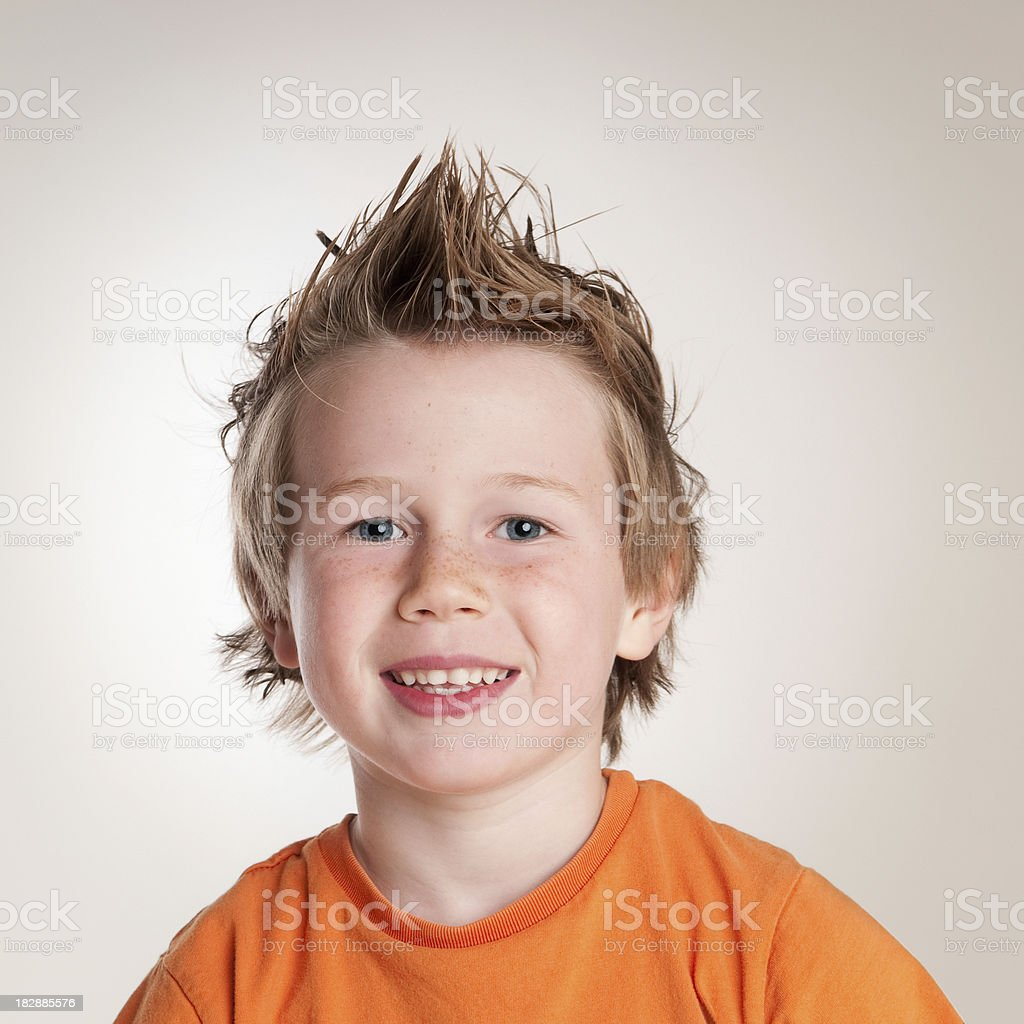 Smiling boy with freckles and spiky hair stock photo