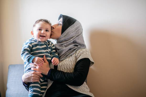 Smiling boy with mom kissing him stock photo