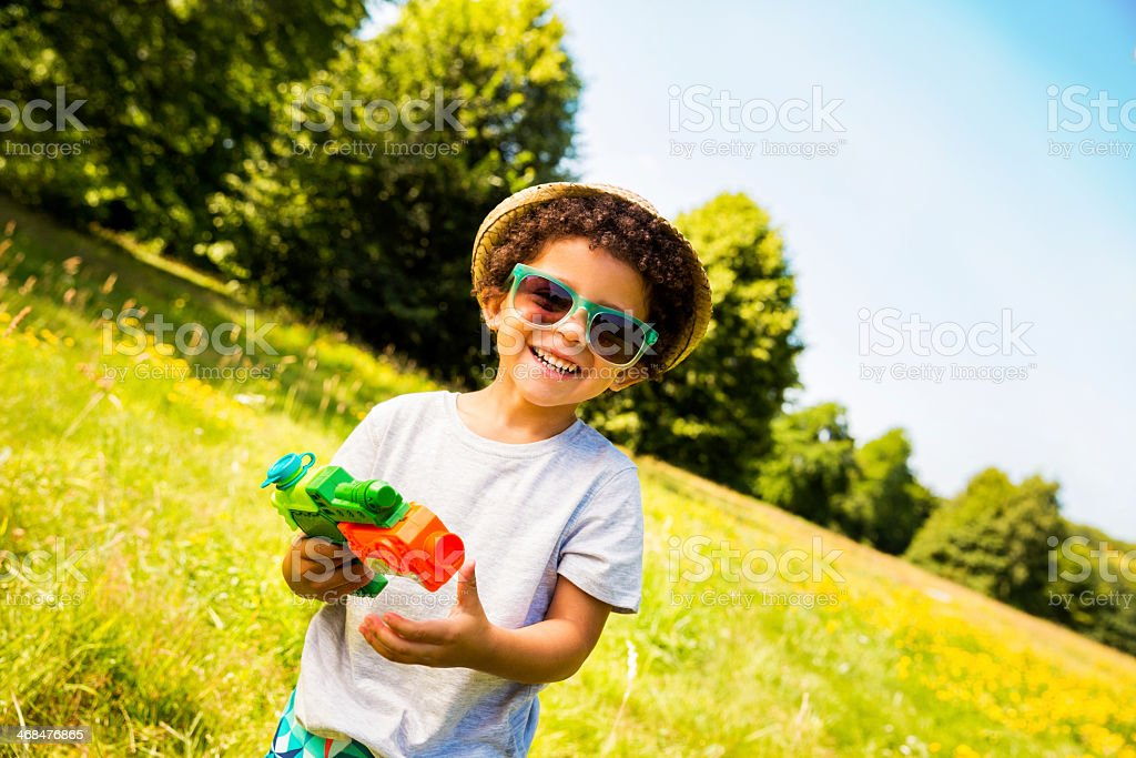 Smiling boy with squirt gun in park royalty-free stock photo