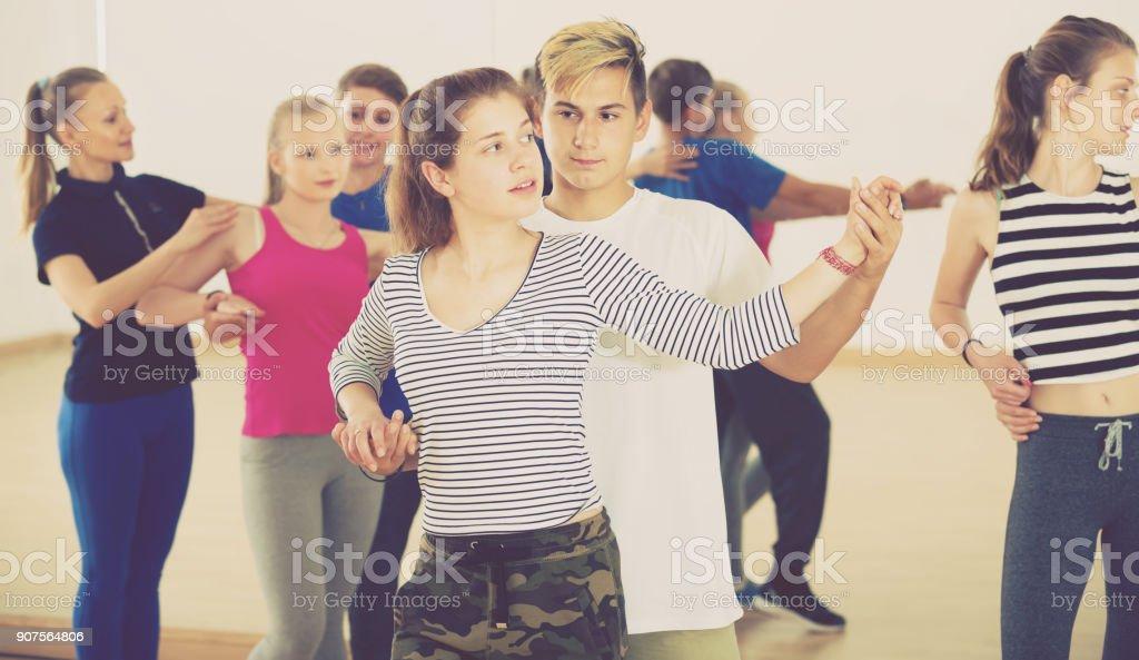 Smiling boys and girls dancing salsa stock photo