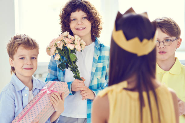 Smiling boys giving presents to girl Group of little boy with gifts and flowers congratulating little girl in crown on birthday group of friends giving gifts to the birthday girl stock pictures, royalty-free photos & images