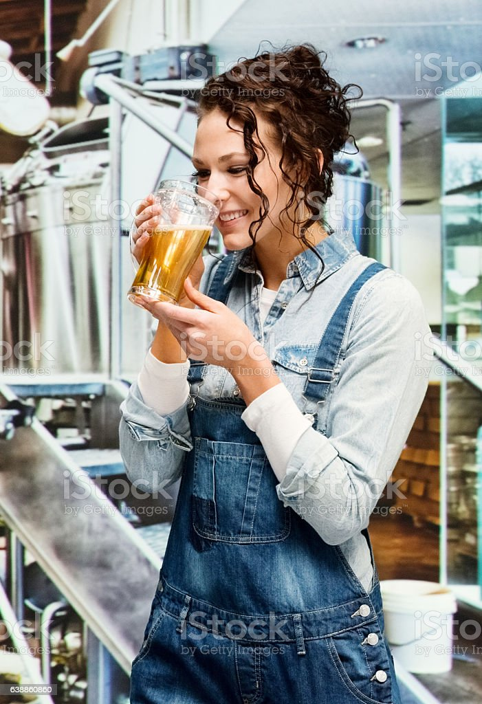 Smiling  brewmaster drinking beer in brewery stock photo
