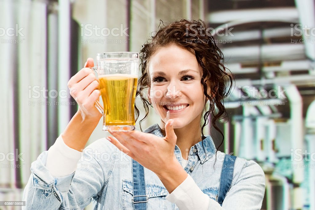Smiling brewmaster holding beer glass in brewery stock photo