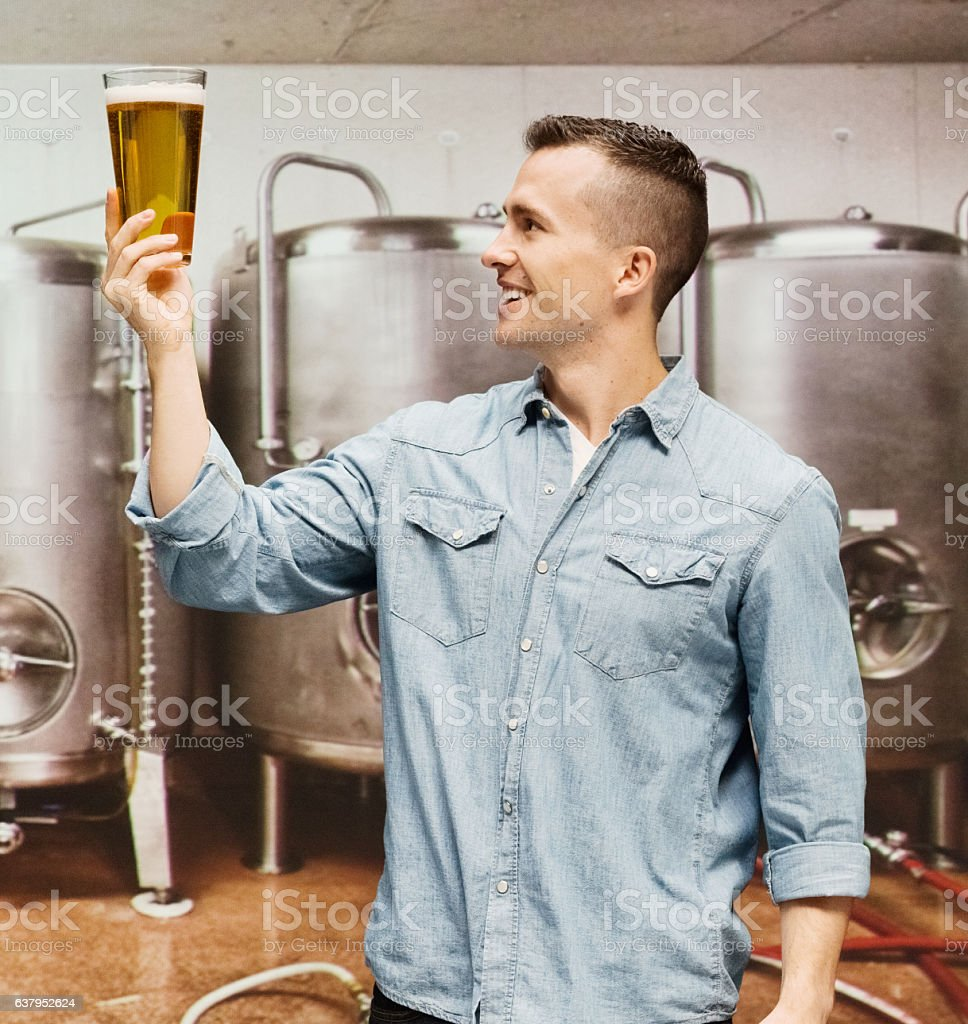 Smiling brewmaster holding beer glass stock photo