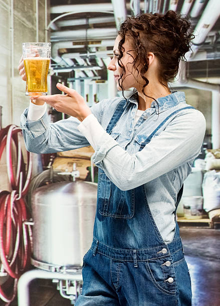 Smiling brewmaster holding drinking glass stock photo