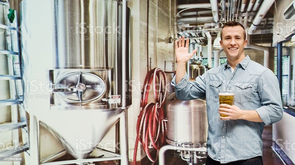 Smiling brewmaster holding glass in industry stock photo