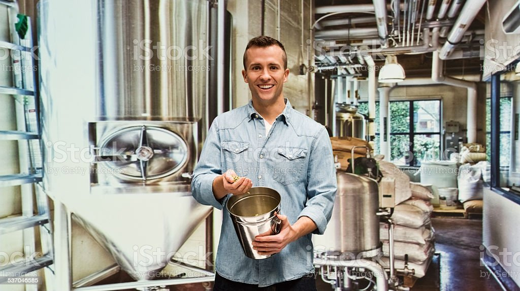Smiling brewmaster in factory stock photo