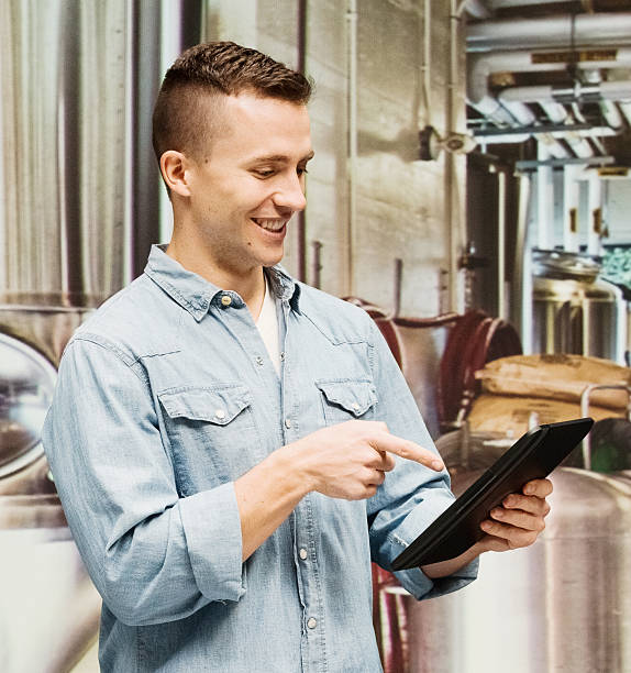Smiling brewmaster pointing at tablet in brewery stock photo