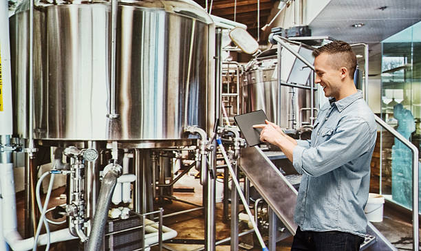 Smiling brewmaster pointing at tablet in industry stock photo