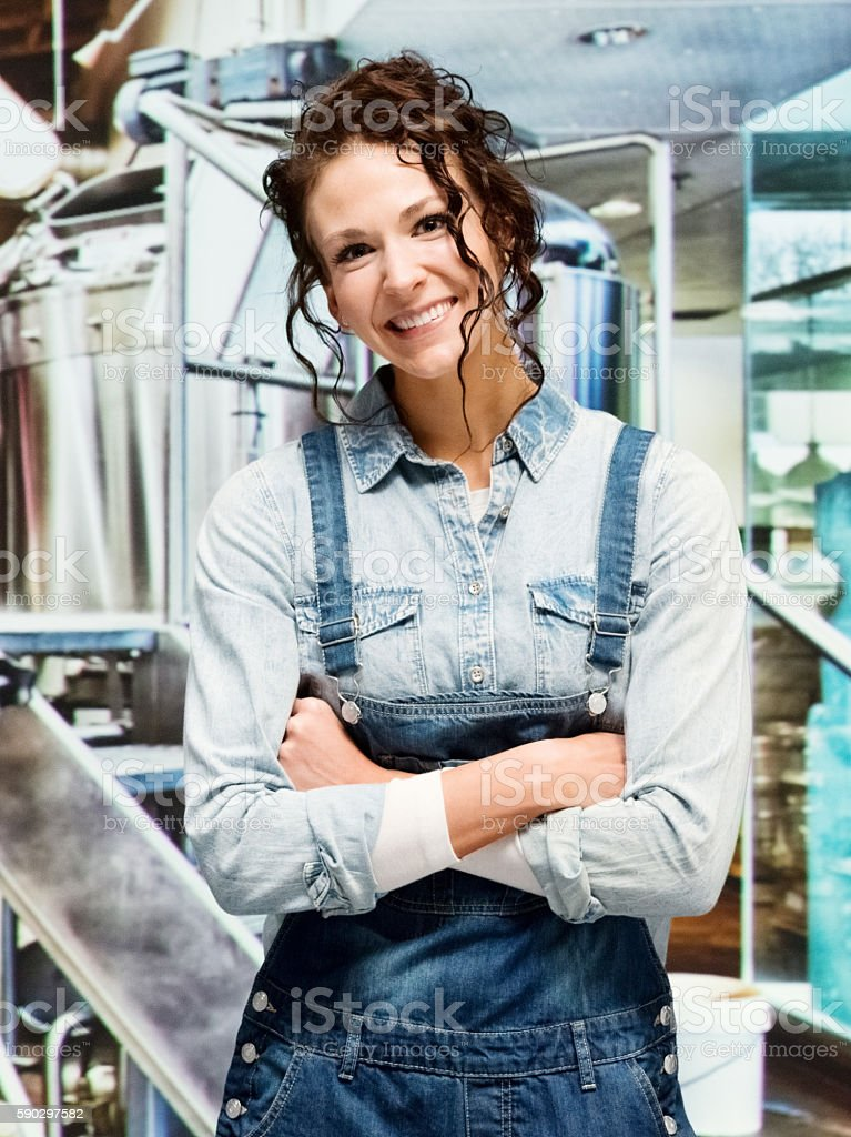 Smiling brewmaster standing in brewery royaltyfri bildbanksbilder