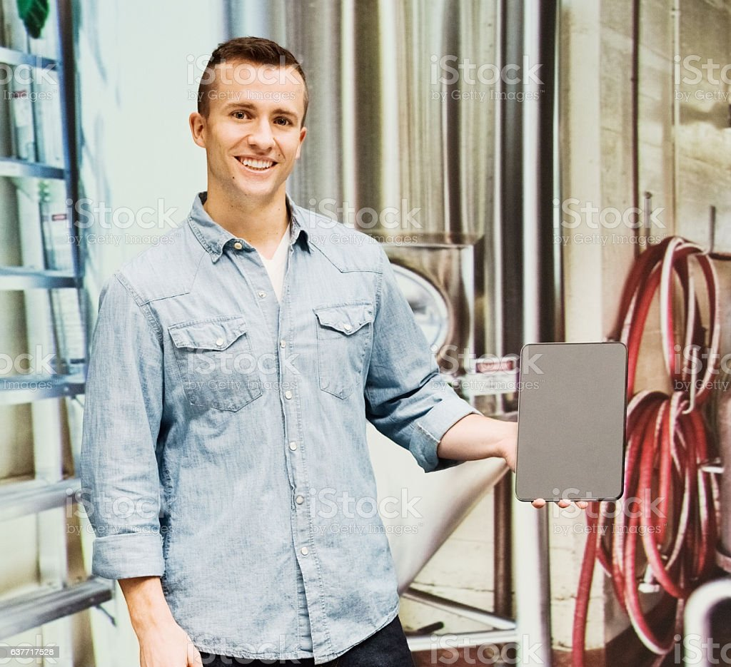 Smiling brewmaster using tablet in brewery stock photo