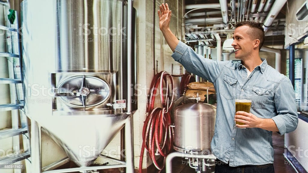 Smiling brewmaster waving hand & holding beer glass stock photo