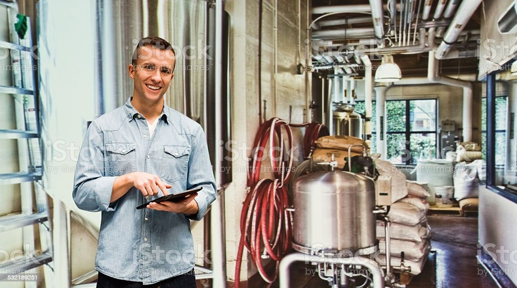 Smiling brewmaster working on tablet stock photo