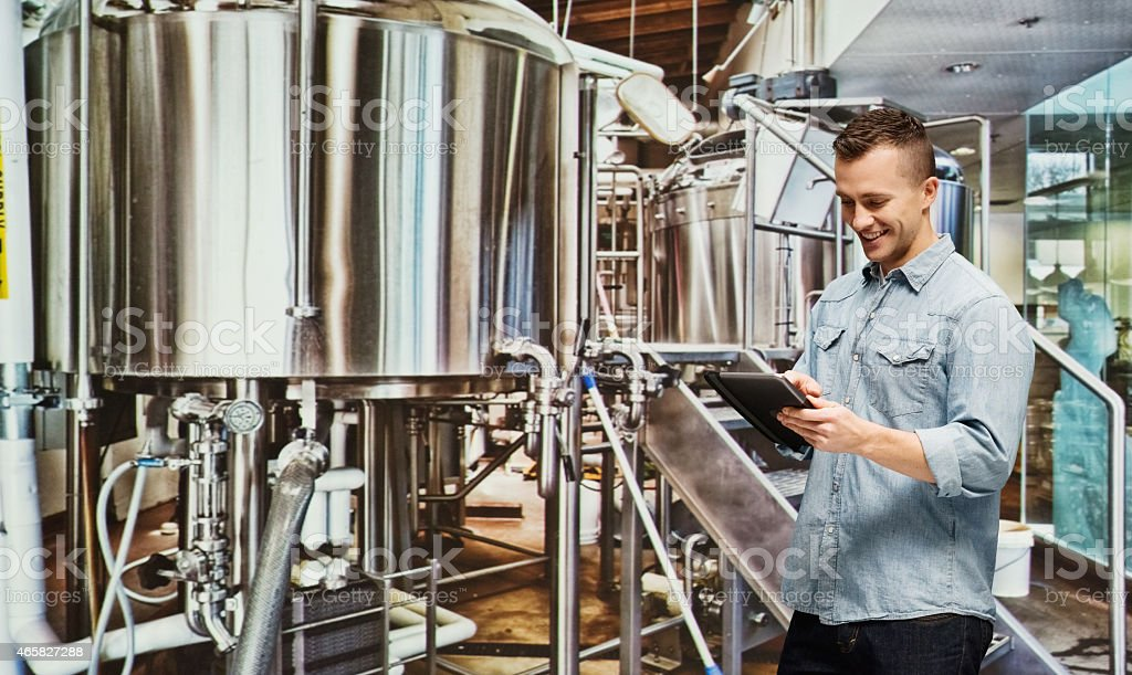 Smiling brewmaster working with tablet stock photo