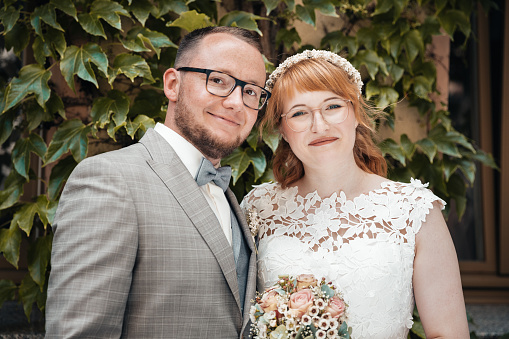 Smiling bridal couple in front of green foliage