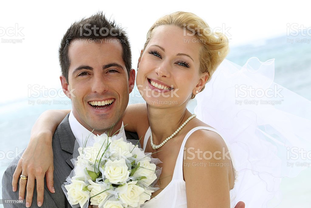 Smiling bridal couple with bouquet of flowers stock photo
