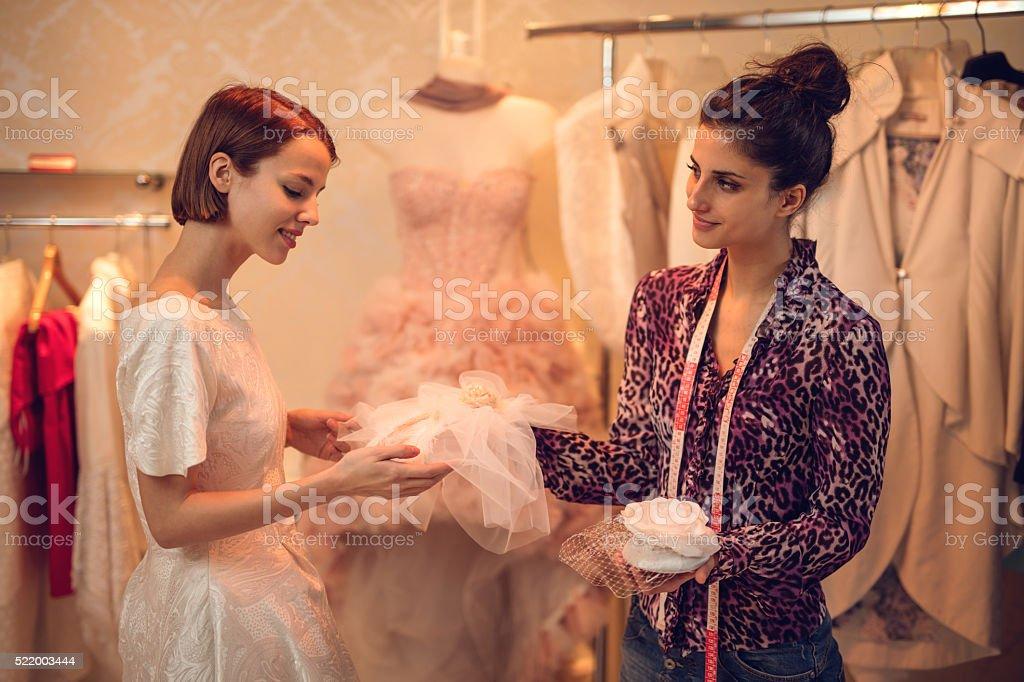 Smiling bride choosing wedding hat in clothing store. stock photo
