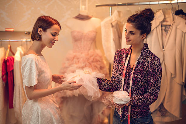 Smiling bride choosing wedding hat in clothing store. stock photo
