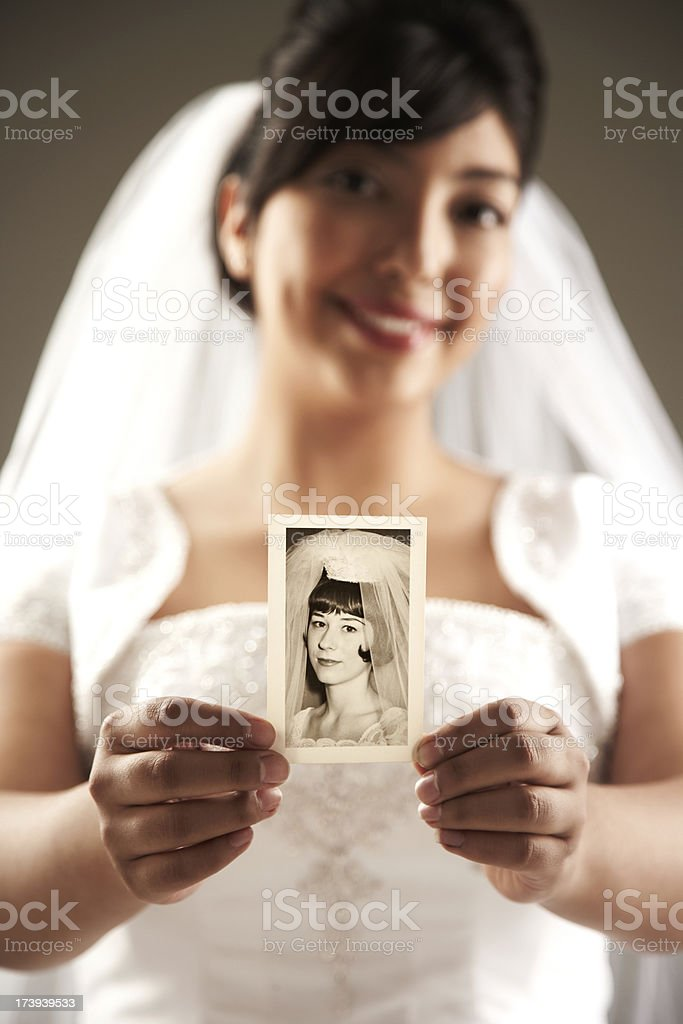 Smiling Bride Holding Up a Vintage Photograph to the Camera. royalty-free stock photo