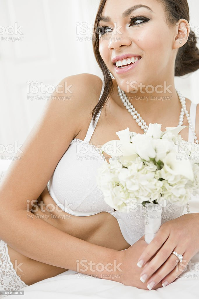 Smiling bride in lingerie laying on bed royalty-free stock photo