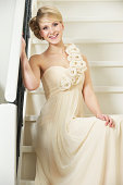 Portrait of a happy bride smiling and sitting on staircase in white wedding dress