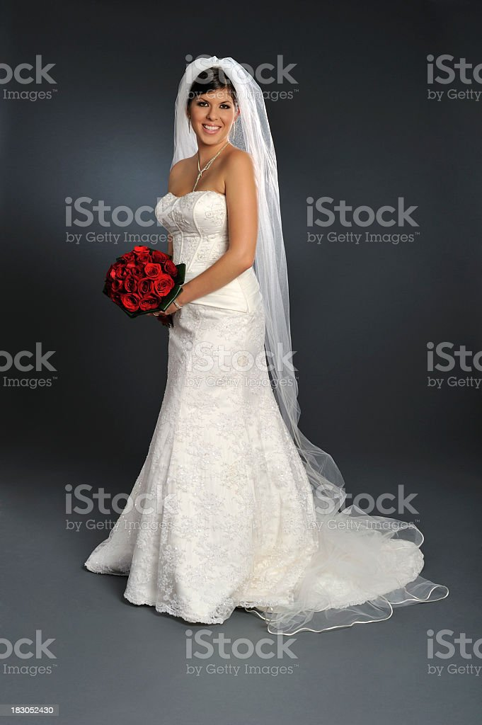 Smiling bride in wedding gown holding bouquet of roses stock photo