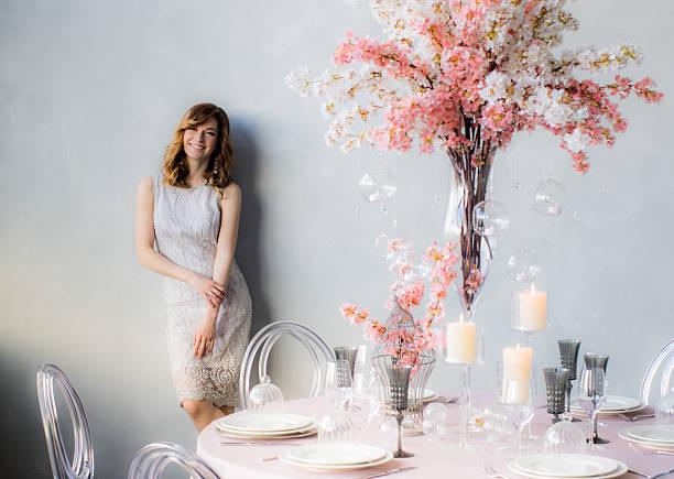smiling bride near the wall and wedding decorations - kleid mit verzierung stock-fotos und bilder