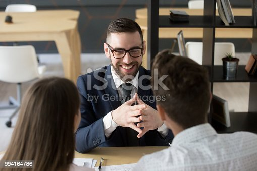 994164754istockphoto Smiling broker laughing consulting clients in office 994164786
