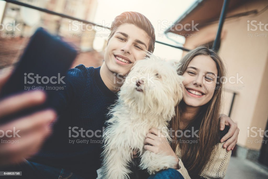 Smiling Brother and Sister Taking Selfie with Their Dog stock photo