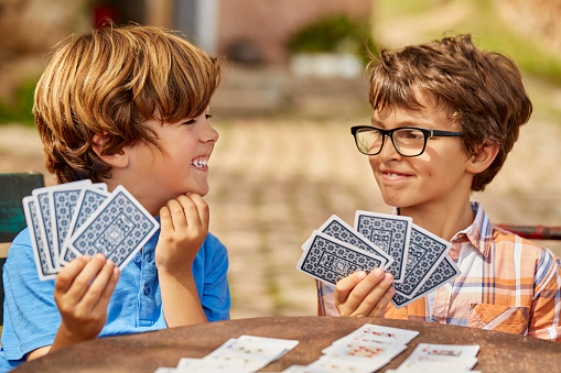 Smiling brothers playing cards at table. Siblings are enjoying leisure game. They are wearing casuals.