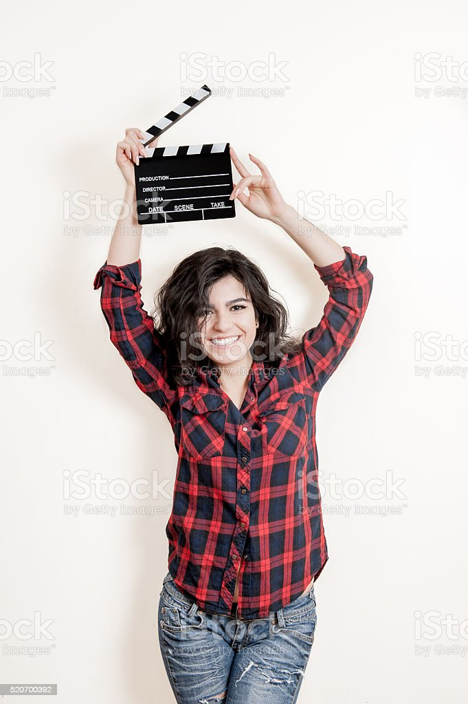 Smiling brunette actress with movie clapper board up stock photo