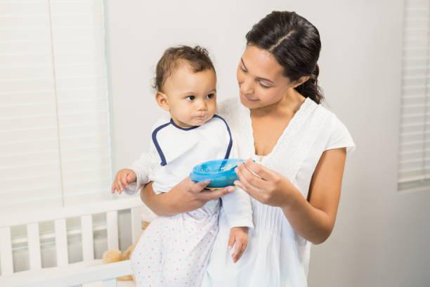 lächelnde brünette fütterung baby - langes lätzchen stock-fotos und bilder