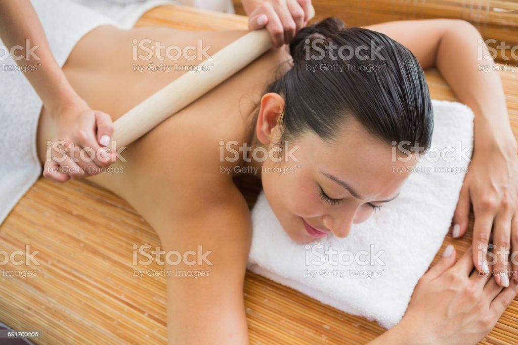Smiling brunette getting a bamboo massage stock photo