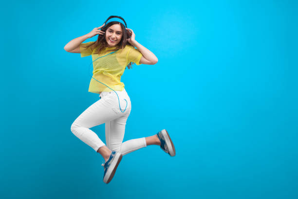lächelnde brünette mädchen kopfhörer springen - tanz make up stock-fotos und bilder