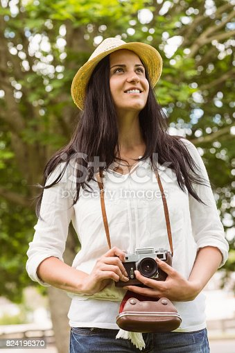 Smiling brunette holding old fashioned camera in the park