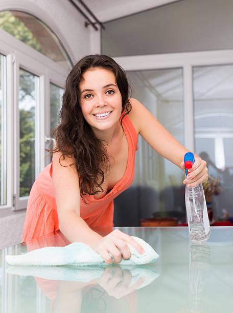 lächeln, brünett houswife reinigung möbel - glaswaschtisch stock-fotos und bilder