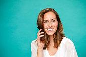 Smiling brunette in white top in blue studio
