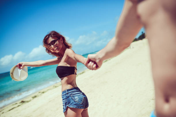 smiling brunette leading her boyfriend toward the ocean - jean shorts stock photos and pictures