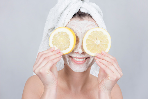 istock Smiling brunette woman holding two slice of lemon in front of her face. woman with moisturizing facial mask. Beauty and skin care concept. 912862714